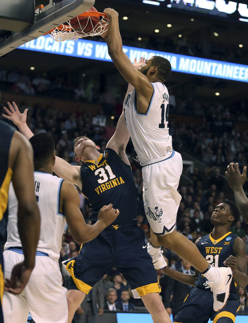 Villanova's Omari Spellman, right, dunks over West Virginia's Logan Routt during the second half of an NCAA men's college basketball tournament regional semifinal Friday, March 23, 2018, in Boston ...