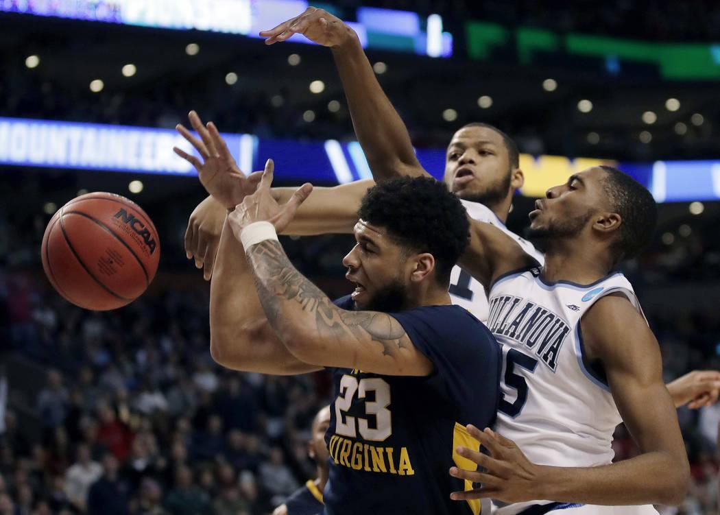 Villanova's Omari Spellman, rear, and Mikal Bridges, right, defend against West Virginia's Esa Ahmad during the second half of an NCAA men's college basketball tournament regional semifinal Friday ...