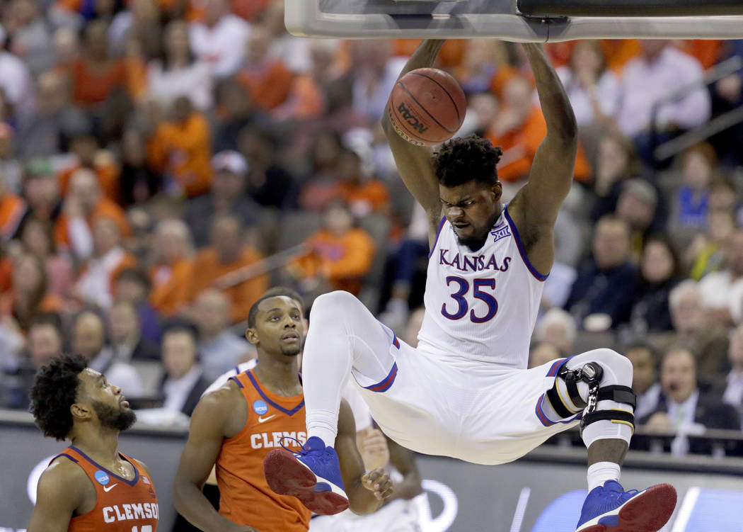 Kansas' Udoka Azubuike (35) dunks as Clemson's Gabe DeVoe, left, and Aamir Simms watch during the second half of a regional semifinal game in the NCAA men's college basketball tournament Friday, M ...
