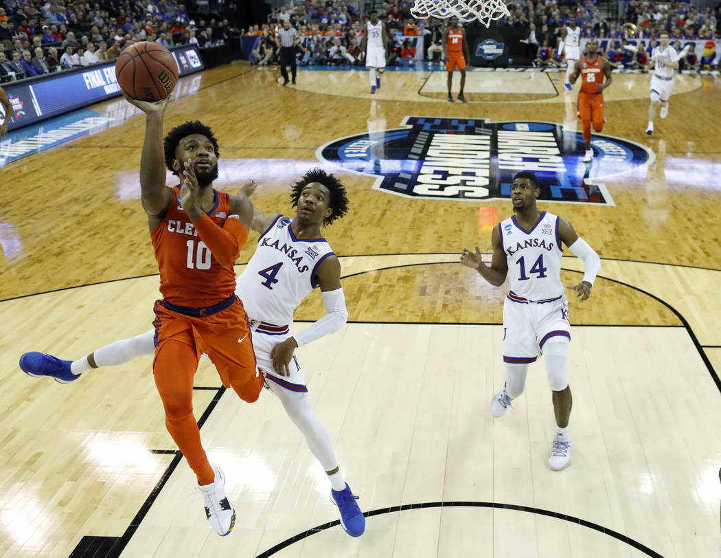 Clemson's Gabe DeVoe (10) heads to the basket as Kansas' Devonte' Graham (4) and Malik Newman defend during the second half of a regional semifinal game in the NCAA men's college basketball tourna ...