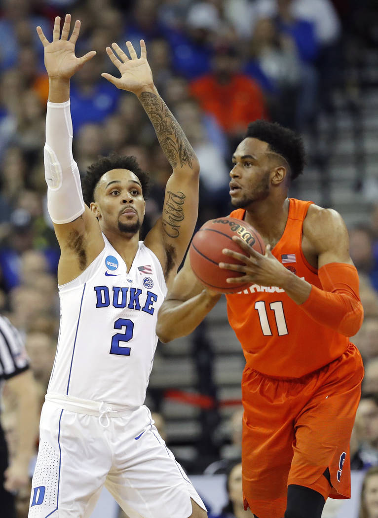 Syracuse's Oshae Brissett (11) passes as Duke's Gary Trent Jr. (2) defends during the first half of a regional semifinal game in the NCAA men's college basketball tournament Friday, March 23, 2018 ...