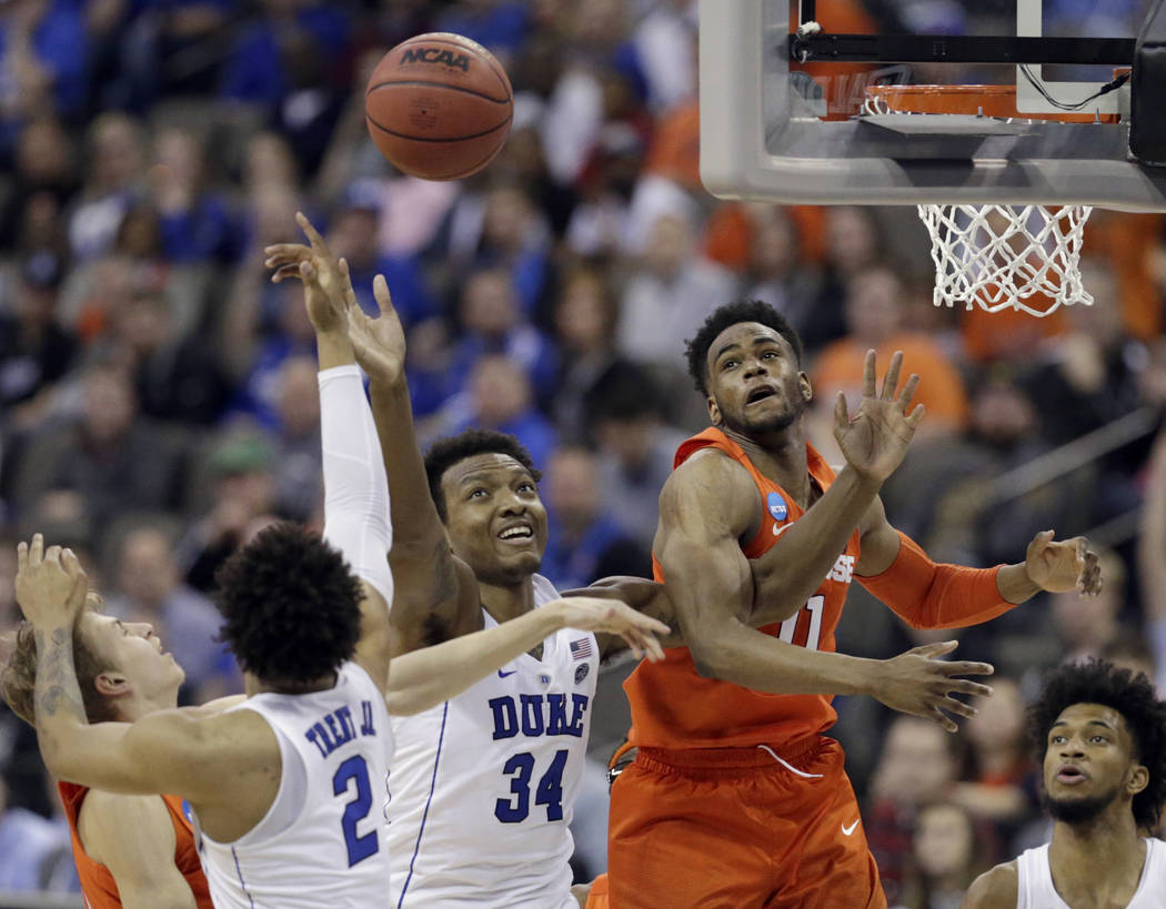 Duke's Gary Trent Jr. (2), Wendell Carter Jr (34) and Syracuse's Oshae Brissett, right, reach for a rebound during the second half of a regional semifinal game in the NCAA men's college basketball ...