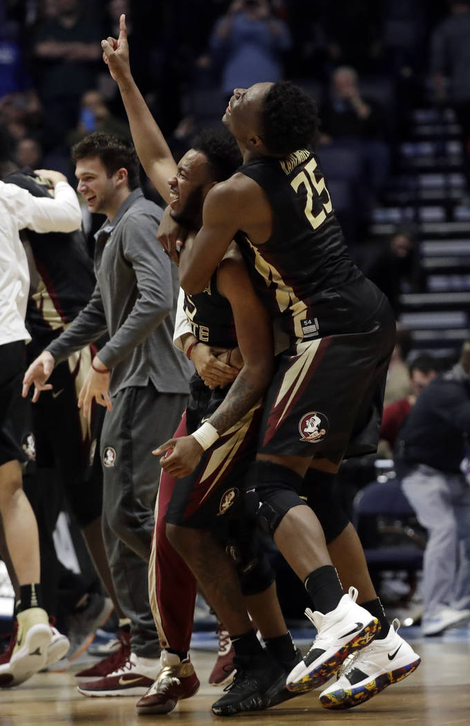 Florida State guard PJ Savoy (5) carries forward Mfiondu Kabengele (25), after defeating Xavier, during a second-round game in the NCAA college basketball tournament in Nashville, Tenn., Sunday, M ...