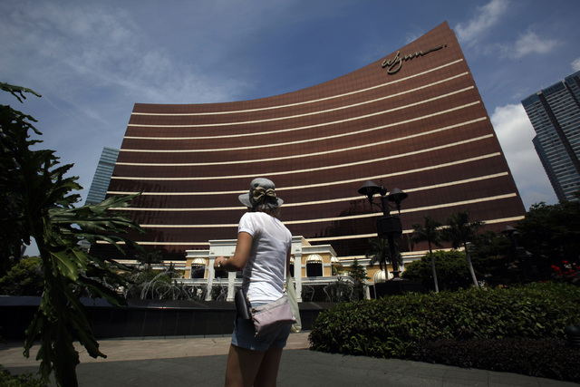 A visitor walks in front of the Wynn Macau resort in Macau June 5, 2012. Macau's casino market experienced a 23.2 percent decline in gaming revenue during October. Wynn Resorts, MGM Resorts Inte ...
