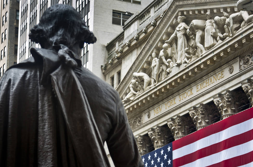 Federal Hall's George Washington statue stands near the flag-covered pillars of the New York Stock Exchange. (Bebeto Matthews/AP, File)