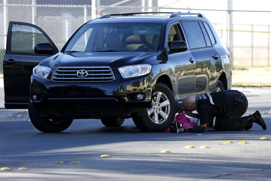 A scene investigator checks underneath a vehicle while investigating a fatal crash near Jack Leavitt Street and Riverdance Avenue in Las Vegas on Friday, March 23, 2018. Andrea Cornejo Las Vegas R ...