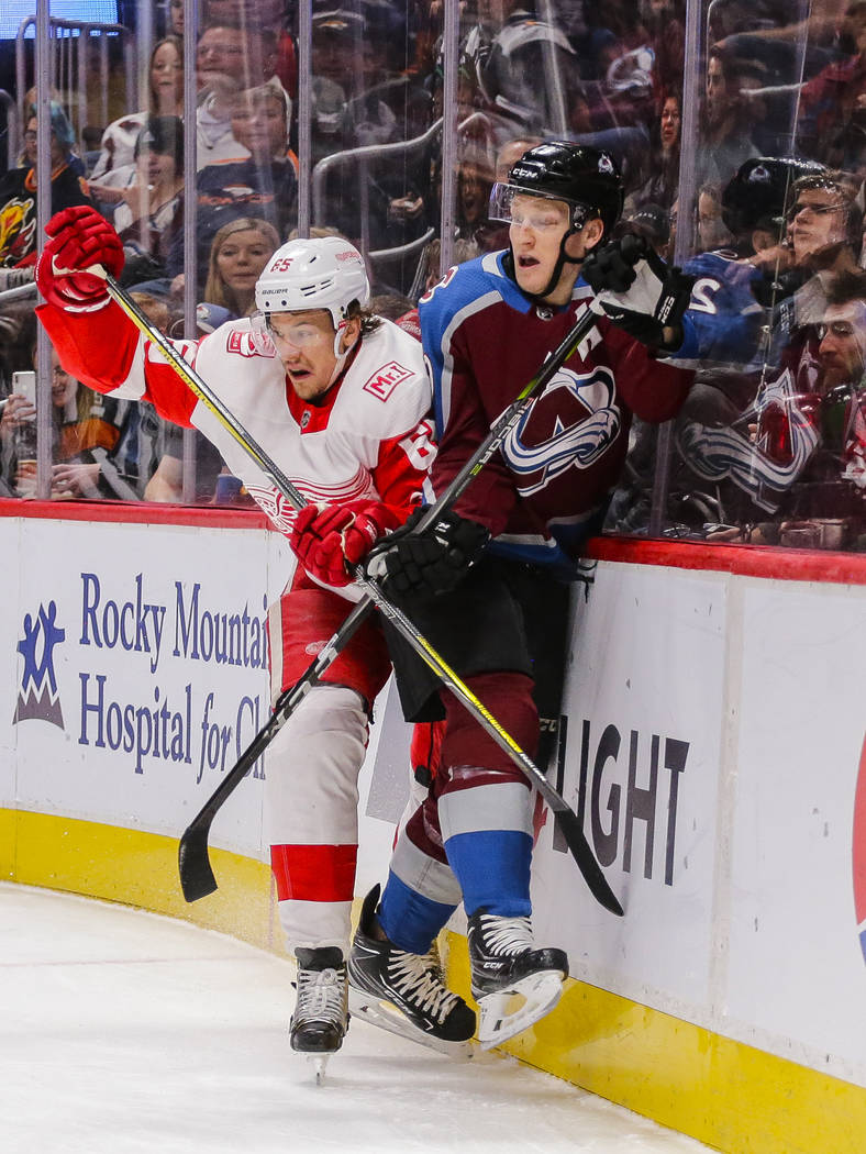 Detroit Red Wings defenseman Danny DeKeyser (65) checks Colorado Avalanche center Nathan MacKinnon (29) into the boards during the first period of an NHL hockey game Sunday, March 18, 2018, in Den ...