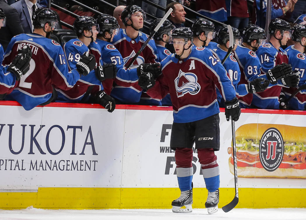 Colorado Avalanche center Nathan MacKinnon is congratulated by teammates on the bench after scoring a goal against the Detroit Red Wings during the second period of an NHL hockey game on Sunday, M ...