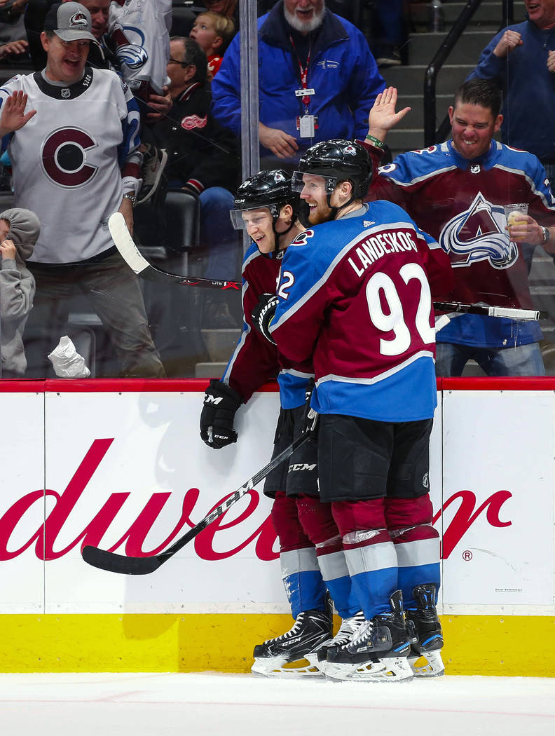 Colorado Avalanche center Nathan MacKinnon, left, is congratulated by teammate Gabriel Landeskog after MacKinnon scored his second goal of the NHL hockey game against the Detroit Red Wings, during ...