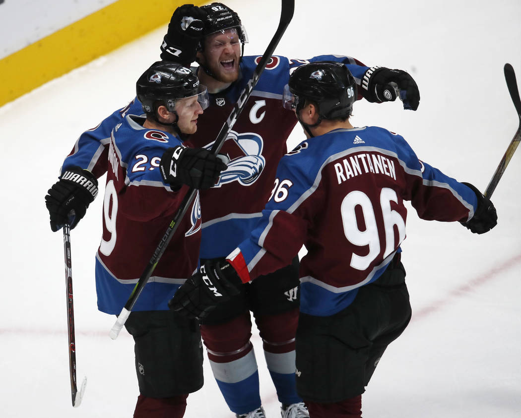 Colorado Avalanche right wing Mikko Rantanen, right, celebrates his goal with center Nathan MacKinnon, front left, and left wing Gabriel Landeskog in the first period of an NHL hockey game against ...
