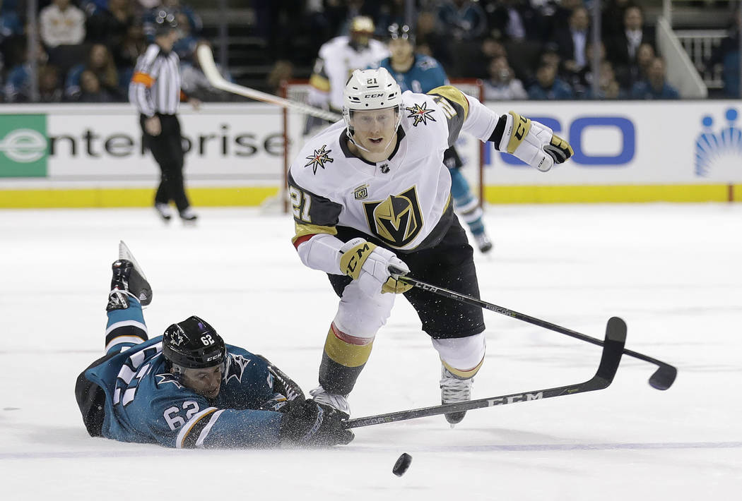 San Jose Sharks' Kevin Labanc, left, dives to clear the puck behind Vegas Golden Knights' Cody Eakin (21) during the first period of an NHL hockey game Thursday, March 22, 2018, in San Jose, Calif ...