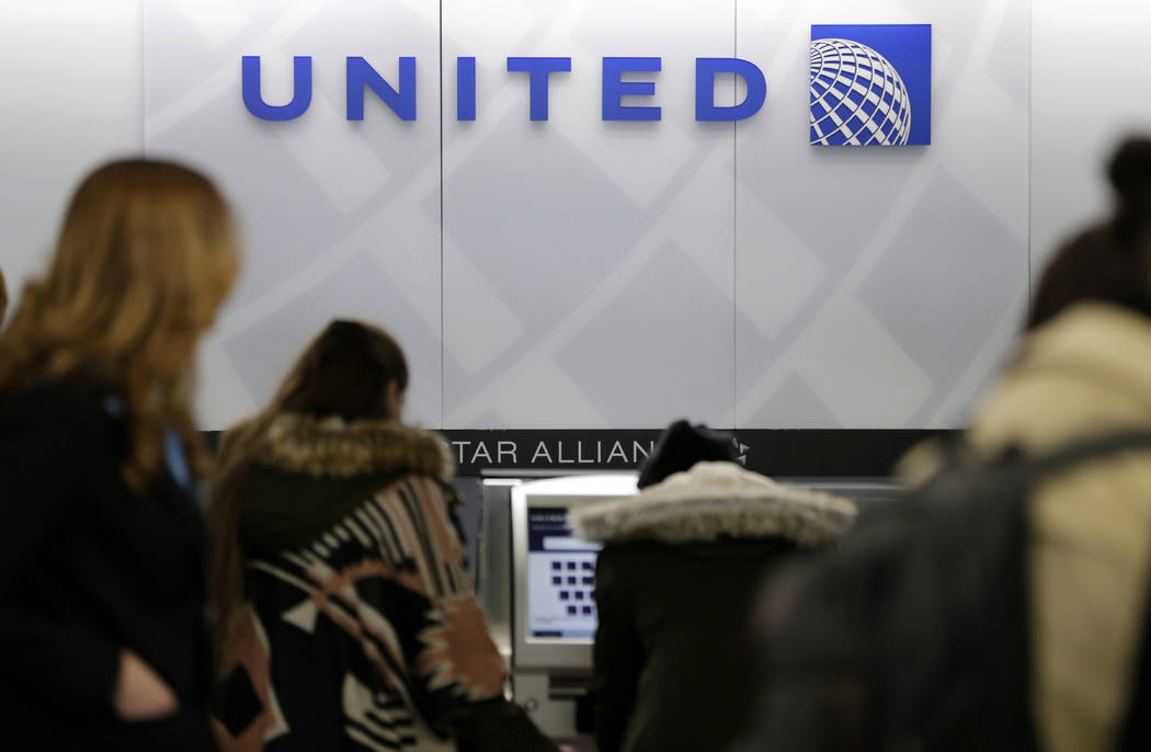 People stand in line at a United Airlines counter at La Guardia Airport in New York