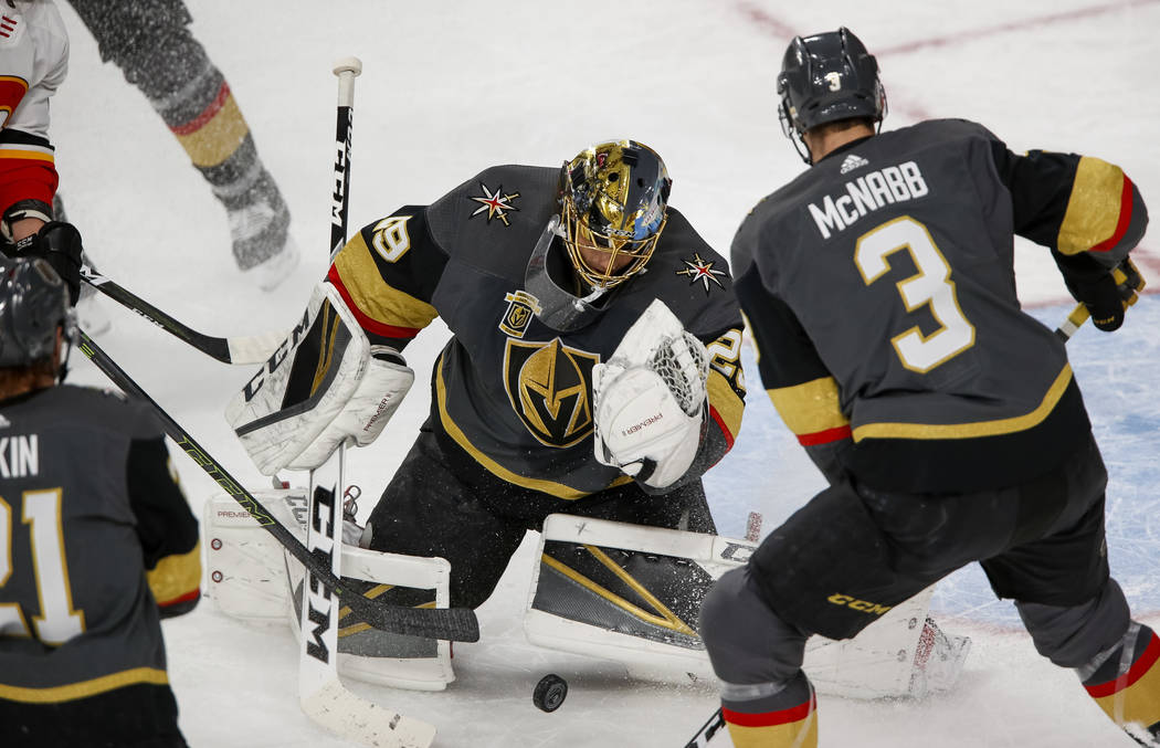 Vegas Golden Knights goaltender Marc-Andre Fleury (29) looks to grab the puck as defenseman Brayden McNabb (3) stands by during the first period of an NHL hockey game between the Golden Knights an ...