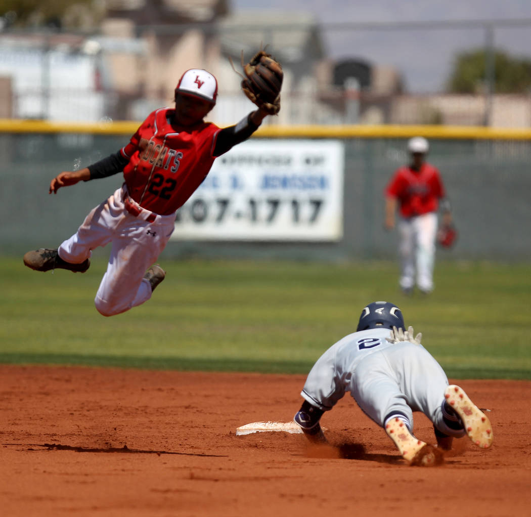 Las Vegas infielder Layne Adaro fields the throw as Rim of the World (Calif.) baserunner Kyler Llewellyn slides safely into second base in the first inning of their baseball game at Las Vegas High ...