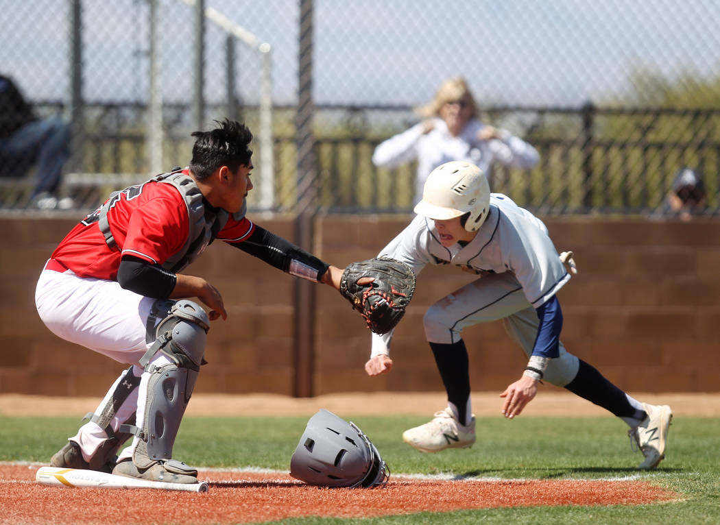 Las Vegas catcher Daniel Jimenez fields the throw as Rim of the World (Calif.) baserunner Colin Morris slides safely into home during the third inning of their baseball game at Las Vegas High Scho ...