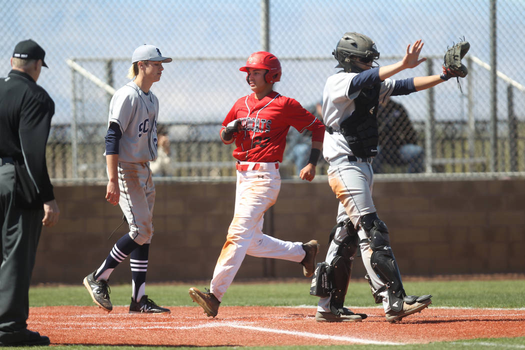 Las Vegas baserunner crosses the plate as the Rim of the World (Calif.) catcher waves off the throw in the fourth inning of their baseball game at Las Vegas High School Monday, March 26, 2018. K.M ...