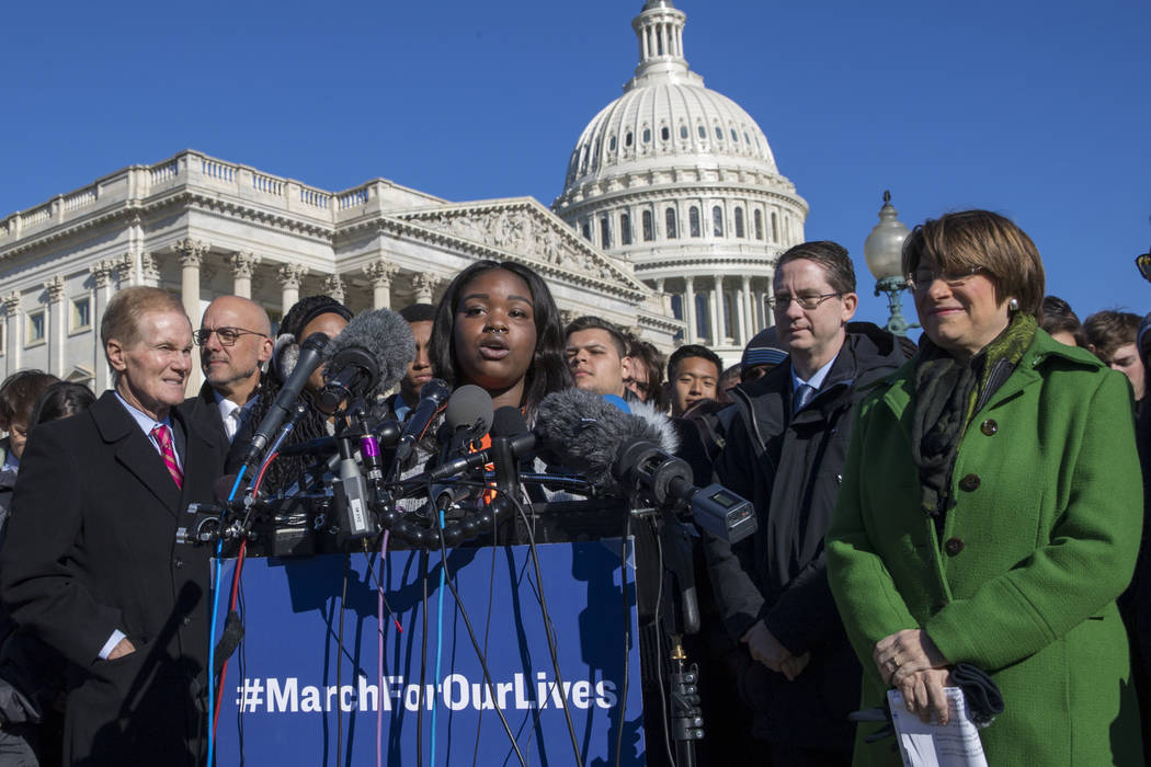 Antiqua Flint, a student at Minneapolis South High School, flanked at left by Sen. Bill Nelson, D-Fla., and Rep. Ted Deutch, D-Fla., and Sen. Amy Klobuchar, D-Minn., far right, joins lawmakers and ...