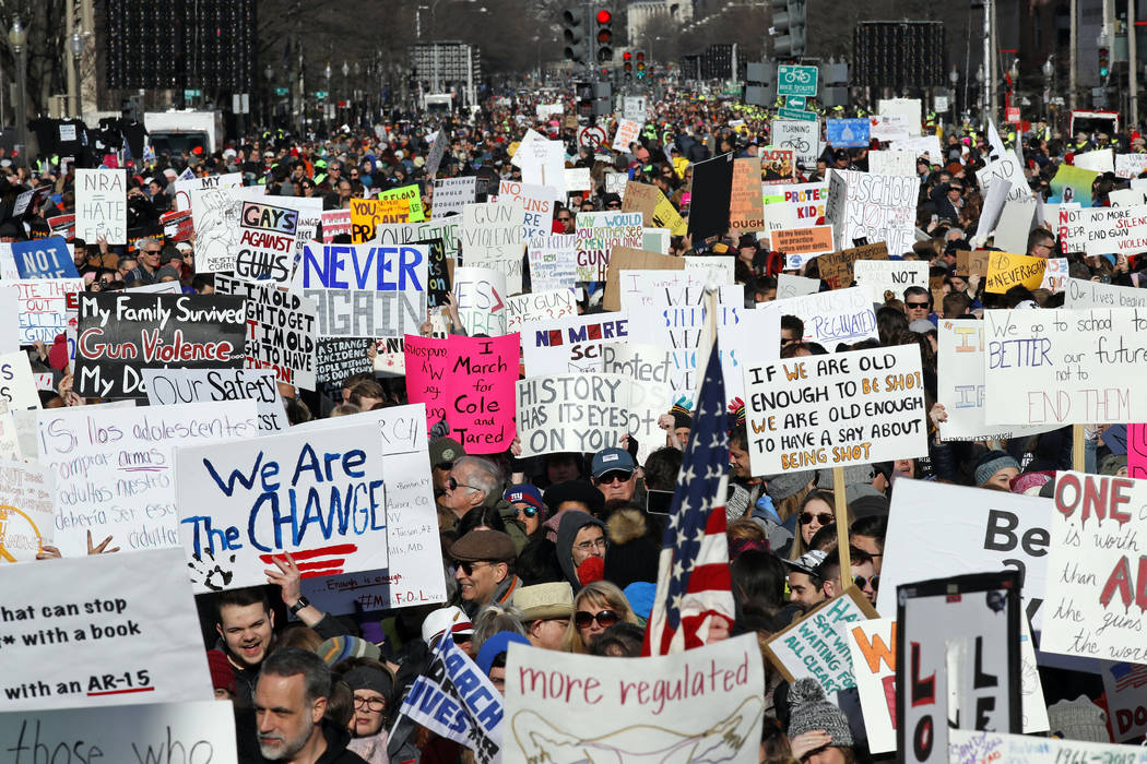"Crowds of people hold signs on Pennsylvania Avenue at the ""March for Our Lives"" rally in support of gun control, Saturday, March 24, 2018, in Washington. (AP Photo/Alex Brandon)"