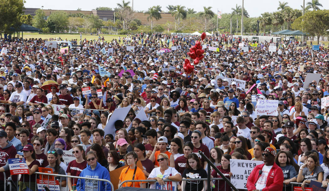 "Participants listen to speakers before taking part in the ""March For Our Lives"" rally Saturday, March 24, 2018, in Parkland, Fla. Thousands of people filled the park near Marjory Stonema ..."