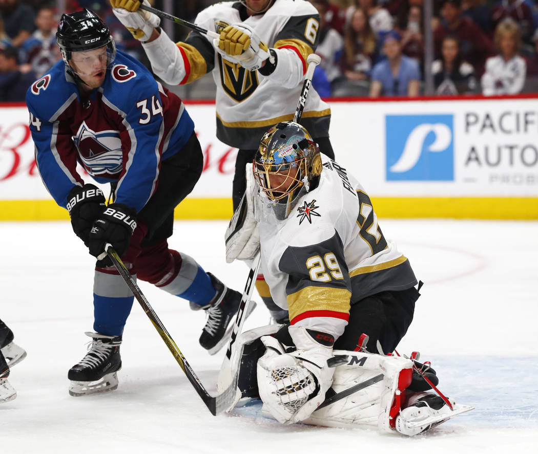 Vegas Golden Knights goaltender Marc-Andre Fleury, right, deflects a redirected shot off the stick of Colorado Avalanche center Carl Soderberg in the first period of an NHL hockey game Saturday, M ...