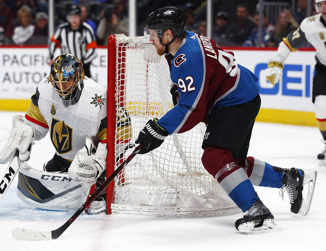 Vegas Golden Knights goaltender Marc-Andre Fleury, left, looks to stop a wraparound shot off the stick of Colorado Avalanche left wing Gabriel Landeskog in the first period of an NHL hockey game S ...