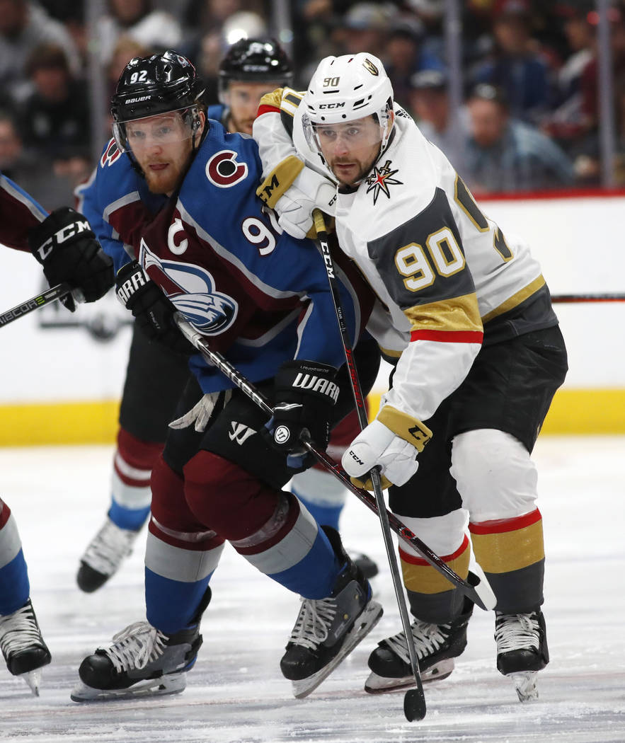 Colorado Avalanche left wing Gabriel Landeskog, left, pursues the puck with Vegas Golden Knights left wing Tomas Tatar in the first period of an NHL hockey game Saturday, March 24, 2018, in Denver ...