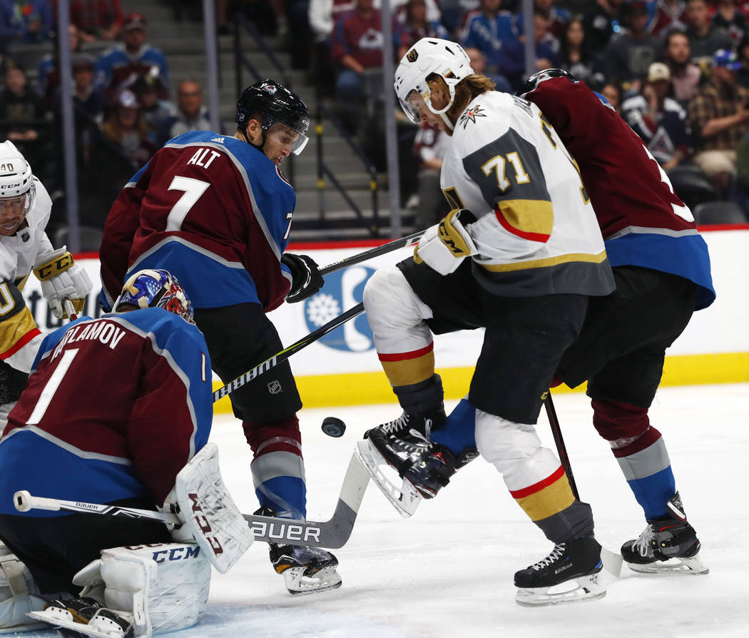 Vegas Golden Knights center William Karlsson (71) gets tangled up with Colorado Avalanche goaltender Semyon Varlamov (1), defenseman Mark Alt (7) and left wing J.T. Compher while trying to redirec ...