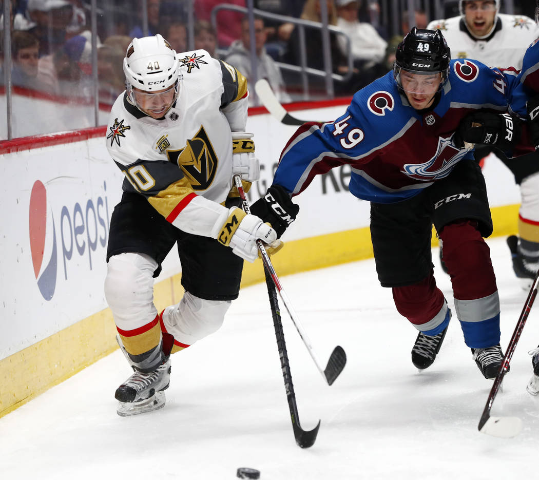 Vegas Golden Knights center Ryan Carpenter, left, fights for control of the puck with Colorado Avalanche defenseman Samuel Girard in the second period of an NHL hockey game Saturday, March 24, 201 ...