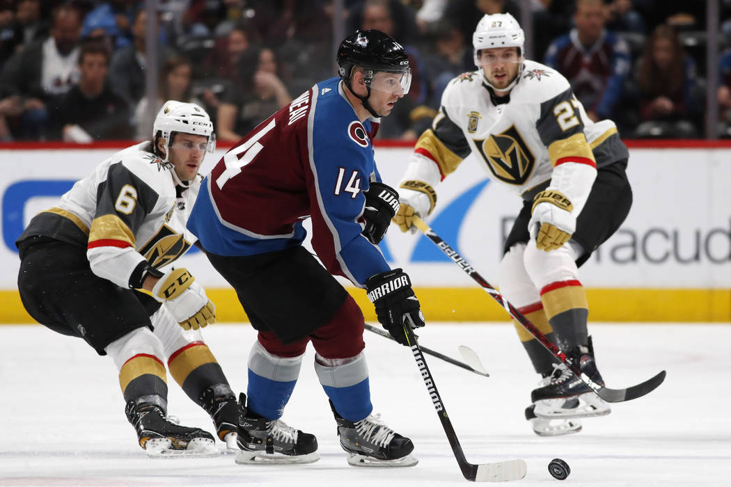 Colorado Avalanche left wing Blake Comeau, front, looks to pass the puck as Vegas Golden Knights defensemen Colin Miller, left, and Shea Theodore skate in during the second period of an NHL hockey ...