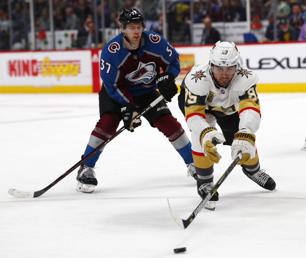 Vegas Golden Knights right wing Alex Tuch, right, reaches out for a loose puck as Colorado Avalanche left wing J.T. Compher skates in during an NHL hockey game Saturday, March 24, 2018, in Denver. ...