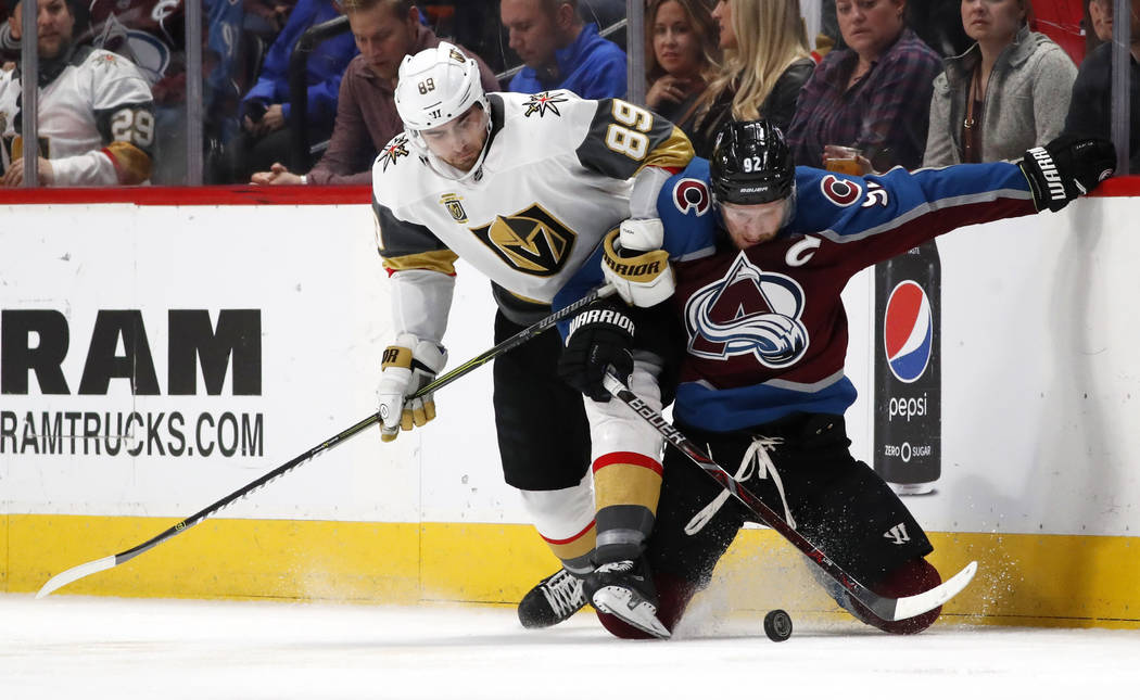 Vegas Golden Knights right wing Alex Tuch, left, fights for control of the puck with Colorado Avalanche left wing Gabriel Landeskog in the third period of an NHL hockey game Saturday, March 24, 20 ...
