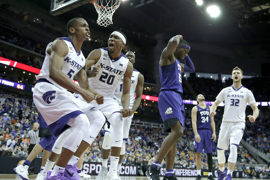 Kansas State's Barry Brown (5) and Xavier Sneed (20) celebrate after a basket during the second half of an NCAA college basketball game against TCU in the Big 12 men's tournament Thursday, March 8 ...