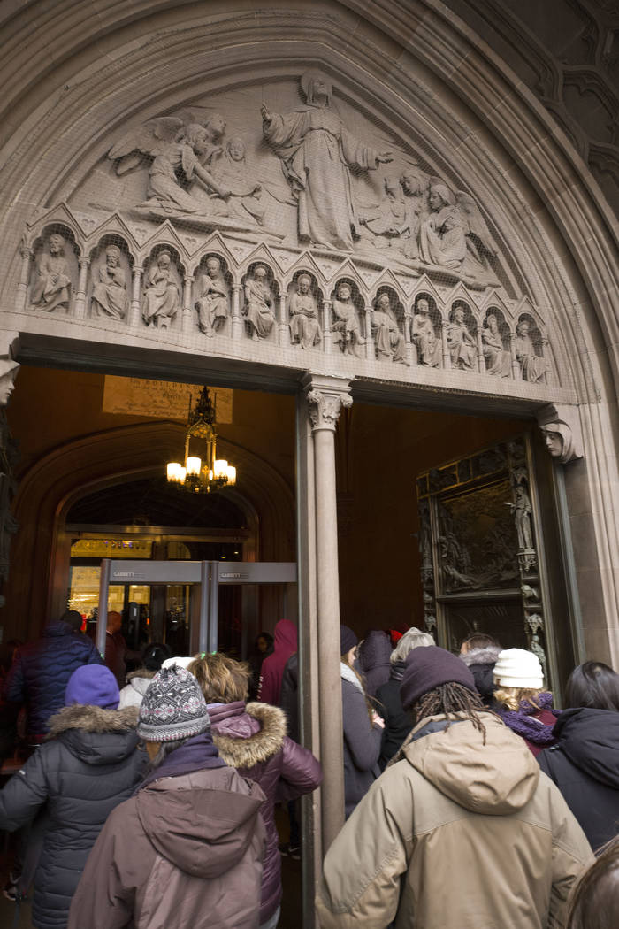 Visitors to Trinity Church wait in line to pass through metal detectors in New York, March 16, 2018. (AP Photo/Mark Lennihan)