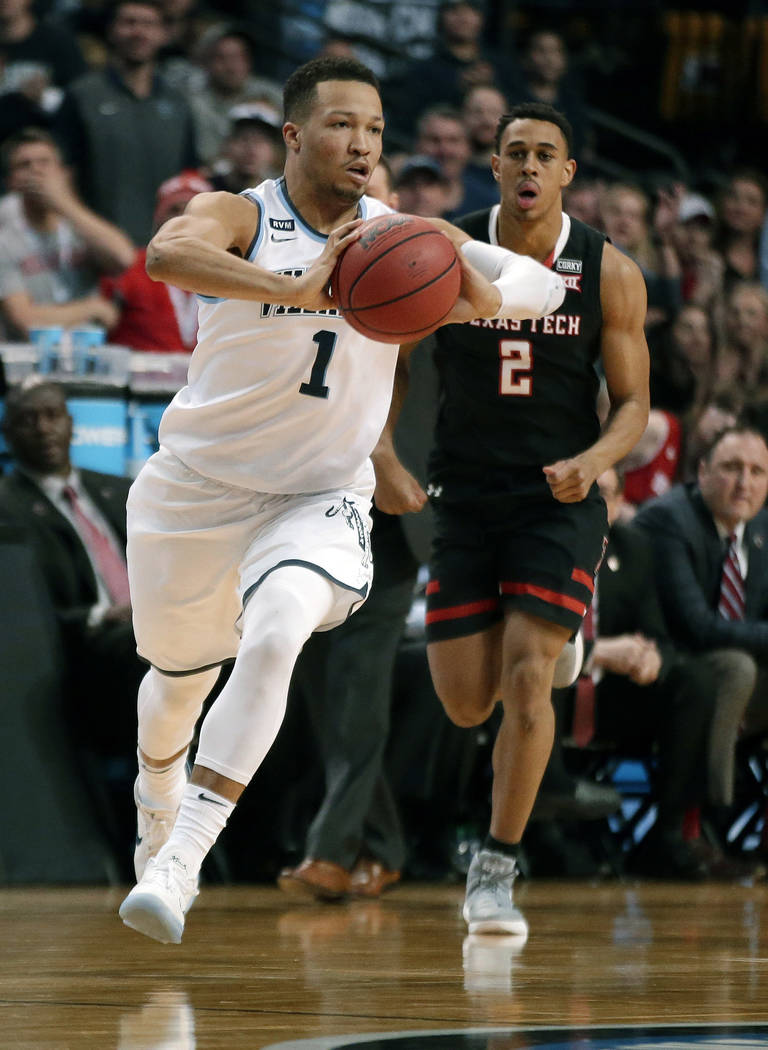 Villanova's Jalen Brunson, front, passes the ball in front of Texas Tech's Zhaire Smith during the second half of an NCAA men's college basketball tournament regional final, Sunday, March 25, 2018 ...