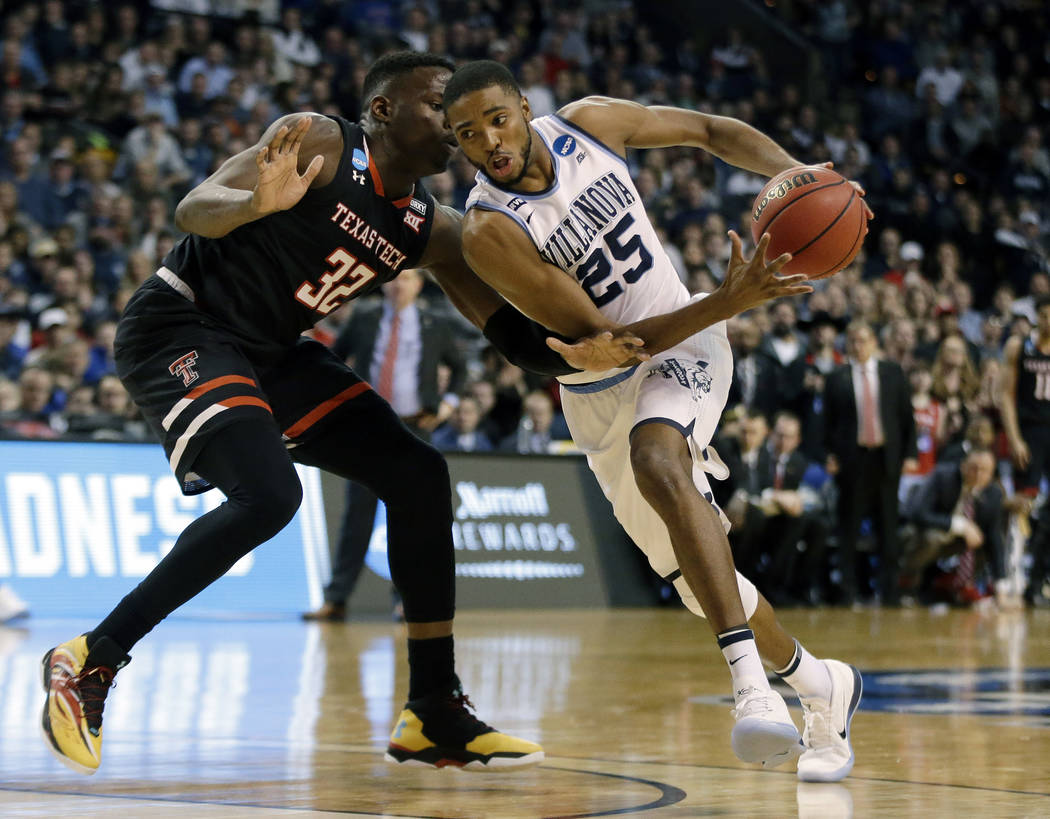 Villanova's Mikal Bridges, right, tries to drive past Texas Tech's Norense Odiase, left, during the second half of an NCAA men's college basketball tournament regional final, Sunday, March 25, 201 ...