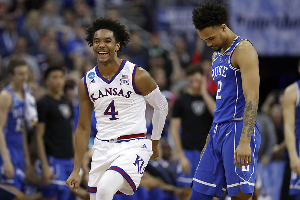 Kansas' Devonte' Graham, left, celebrates as he runs past Duke's Gary Trent Jr. in the final seconds of overtime of a regional final game in the NCAA men's college basketball tournament Sunday, Ma ...