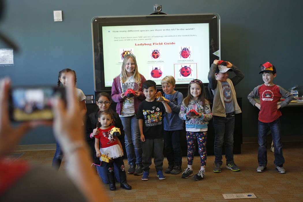 Cadence Taylor takes a photo of children with their paper ladybugs they made in the Young Explorers program at the Clark County Wetlands Park in Las Vegas, Sunday, March 25, 2018. (Rachel Aston La ...
