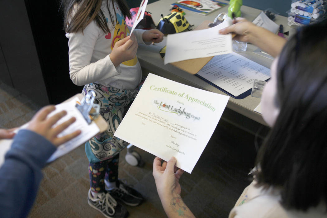 Recreation Assistant Alice Hulslander passes out certificates for completing the day's program at the end of the Young Explorers program at the Clark County Wetlands Park in Las Vegas, Sunday, Mar ...