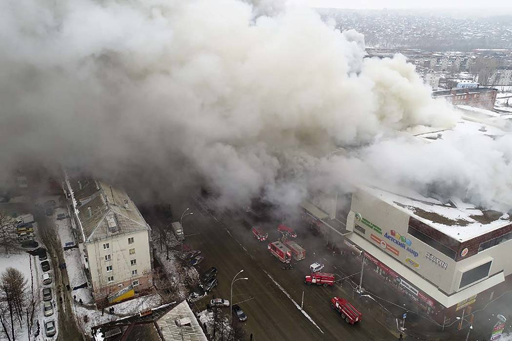 In this Russian Emergency Situations Ministry photo, on Sunday, March 25, 2018, smoke rises above a multistory shopping center in the Siberian city of Kemerovo. At least 64 people have died. (Russ ...