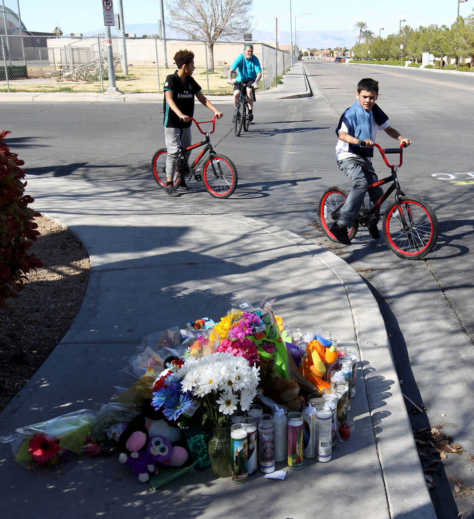 Boys on bicycles pass a makeshift memorial at the corner of Jack Leavitt Street and Riverdance Avenue near Silvestri Junior High School on Monday, March 26, 2018. Niccoli Franklin, 9, was hit and  ...