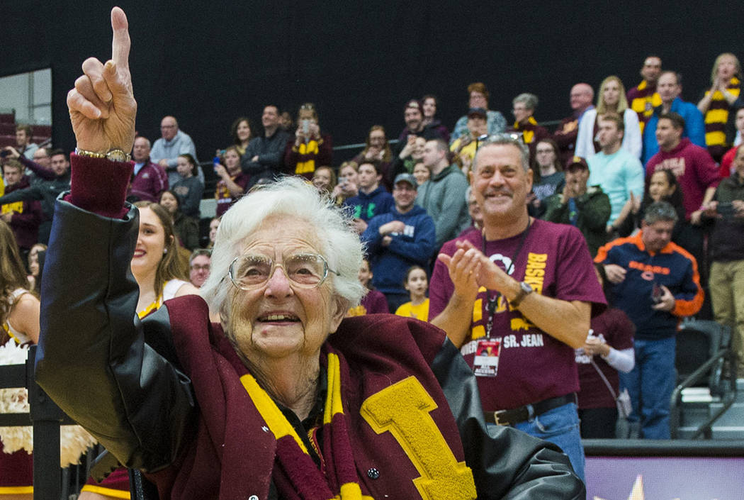 Sister Jean Dolores-Schmidt, the Loyola Ramblers Chaplain, holds up number one as fans chant inside the Gentile Arena, Sunday, March 25, 2018 in Chicago. (Tyler LaRiviere/Chicago Sun-Times via AP)