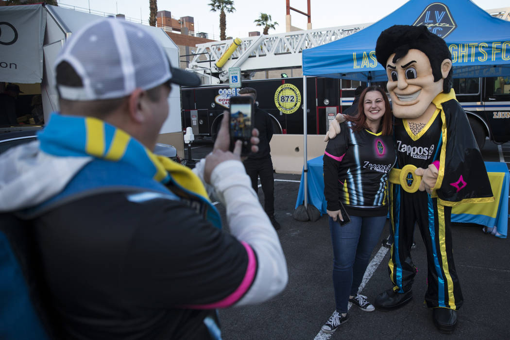 Melissa Zigrosser, center, with Cash the Soccer Rocker, is photographed by her boyfriend Apolo Escobedo during the United Soccer League season home opener game for the Las Vegas Lights FC at Cashm ...