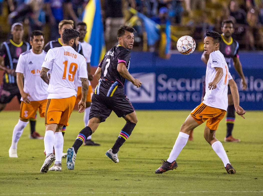 Lights midfielder Carlos Alvarez looks at the ball while Swope Park midfielder Kuzian juggles the ball during the first half of a game against the Swope Park Rangers at Cashman Field in Las Vegas  ...
