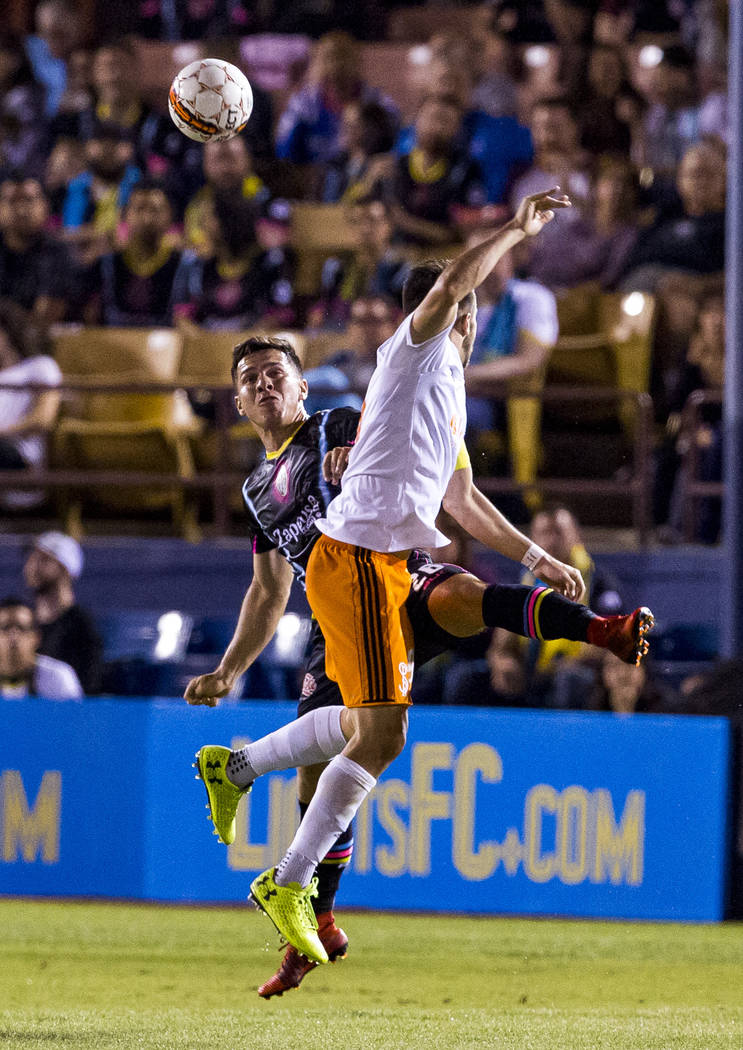 Lights midfielder Julian Portugal and Swope Park midfielder Rodrigo Saravia both go up for the ball during the first half of a game against the Swope Park Rangers at Cashman Field in Las Vegas on  ...
