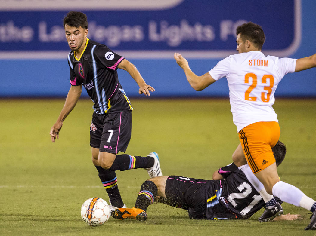 Lights midfielder Carlos Alvarez tries to take the ball away as Swope Park defender Colton Storm as Lights forward Matt Thomas slides on the field during the second half of a United Soccer League  ...