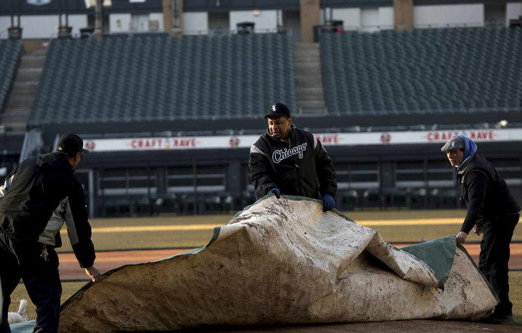 White Sox groundskeeper Nevest Coleman, center, helps Harry Smith Jr., left, and Jerry Powe with the tarp at Guaranteed Rate Field in Chicago,Monday, March 26, 2018. The Chicago Tribune reports th ...