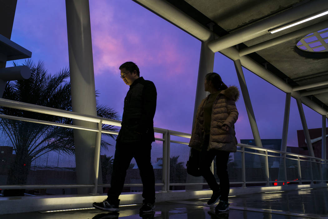 Pedestrians cross a bridge at Las Vegas North Premium Outlets as the sun sets after a long day of rain in Las Vegas on Tuesday, Jan. 9, 2018. (Chase Stevens/Las Vegas Review-Journal) @csstevensphoto