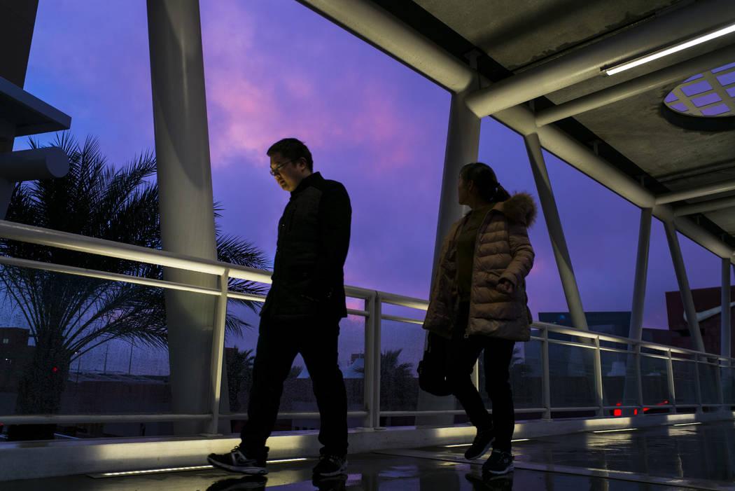 Pedestrians cross a bridge at Las Vegas North Premium Outlets as the sun sets after a long day of rain in Las Vegas on Tuesday, Jan. 9, 2018. (Chase Stevens/Las Vegas Review-Journal) @csstevensphoto