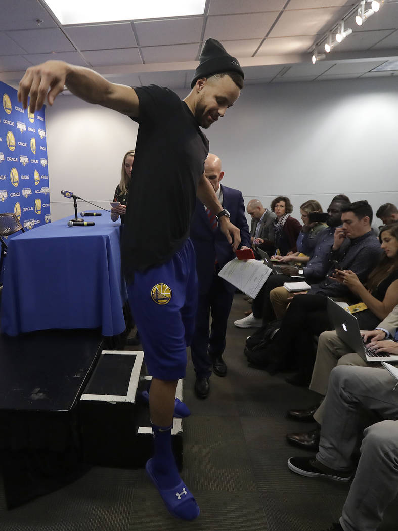 Golden State Warriors guard Stephen Curry walks down a step after speaking at a news conference before an NBA basketball game between the Warriors and the Utah Jazz in Oakland, Calif., Sunday, Mar ...