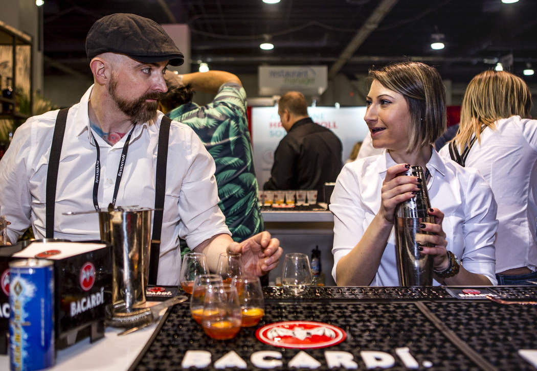 Bacardi bartenders Jimmy McGowan and Jessica Fitzmeyer share a moment while preparing drinks during the Nightclub and Bar Show at the Las Vegas Convention Center on Tuesday, March 27, 2018.  Patri ...